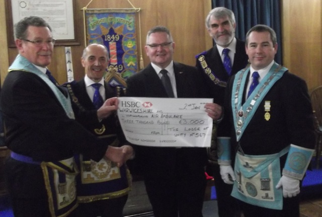 W Bro Watson presents a cheque for £3,000 to Stuart Wilkins for the Warwickshire & Northants Air Ambulance